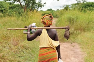 African woman carrying a tool on a grassy path