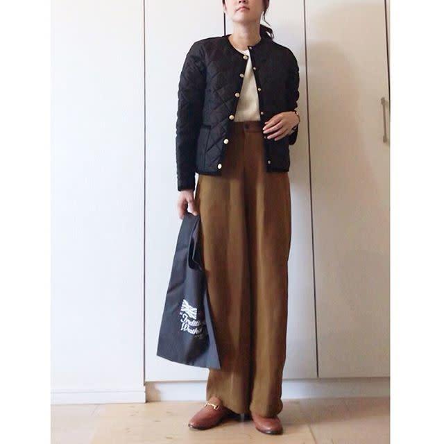 コンパクトな黒のキルティングジャケットにカジュアルなパンツを合わせて大人っぽく