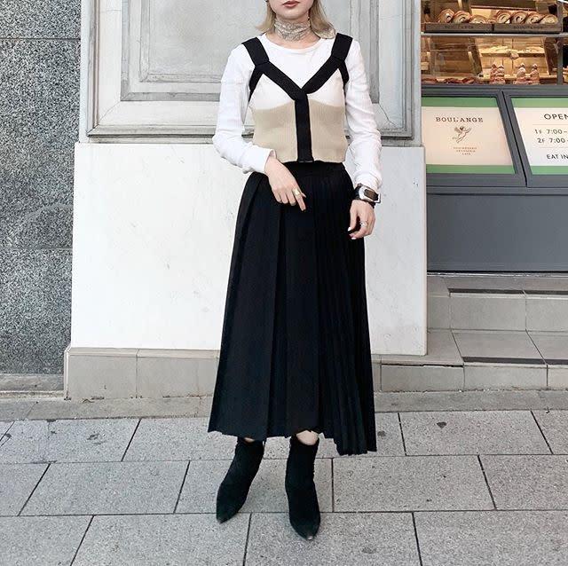 黒のプリーツスカートに辛口なショートブーツを合わせて
