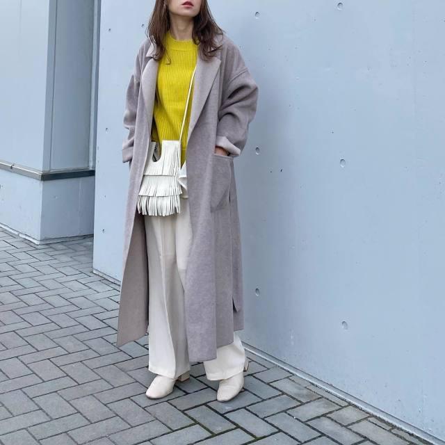 グレージュコートに白パンツを着た女性