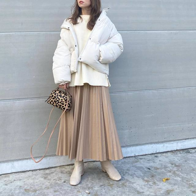 白やベージュ色のダウンジャケットにプリーツスカート&ブーツを組み合わせて