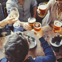 Group of people drinking beer at a bar cheers