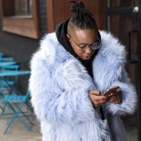 Person in fur coat looking at phone