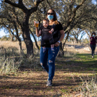 Woman walking with baby and holding a beer