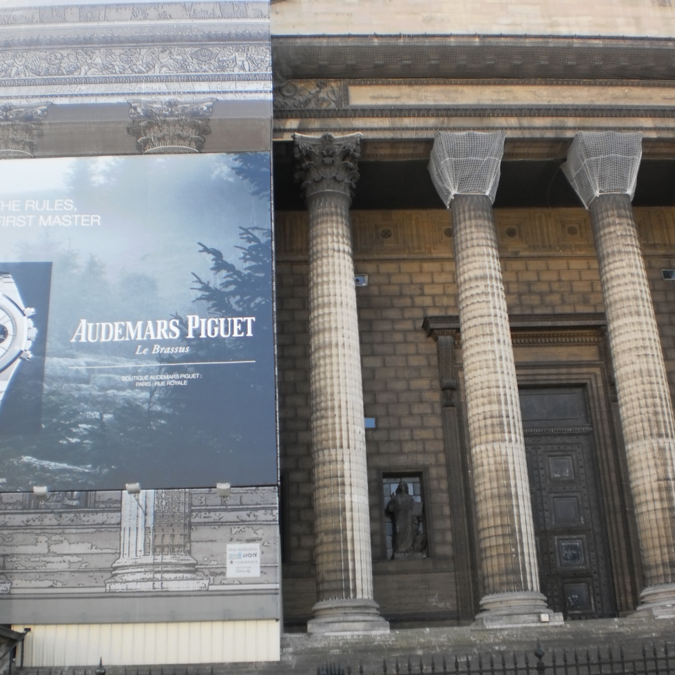 Ad for Audemars Piguet presents a contemporary counterpoint on the facade covering construction work at Place de la Madeleine in Paris