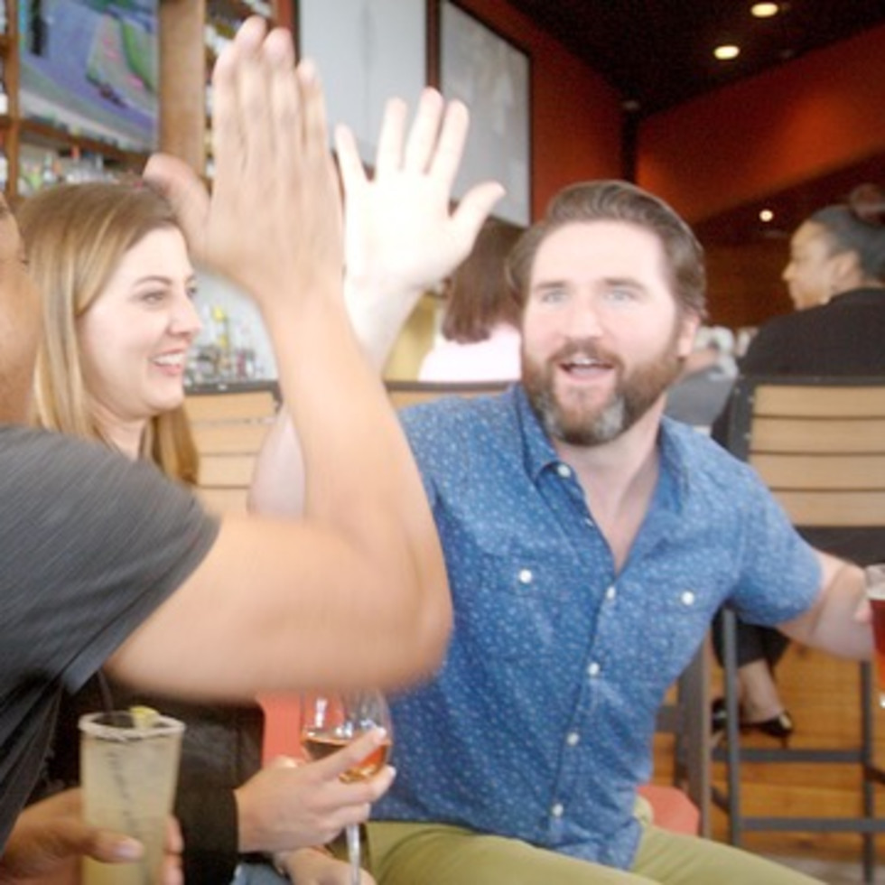 Friends high-fiving at Pinstack