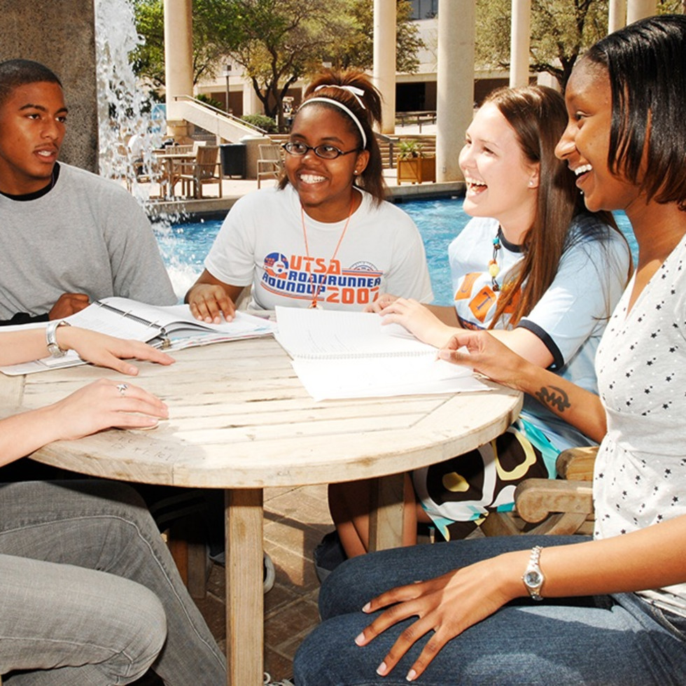 UTSA students in the 2000s enjoy an afternoon near the main campus sombrilla and fountain.