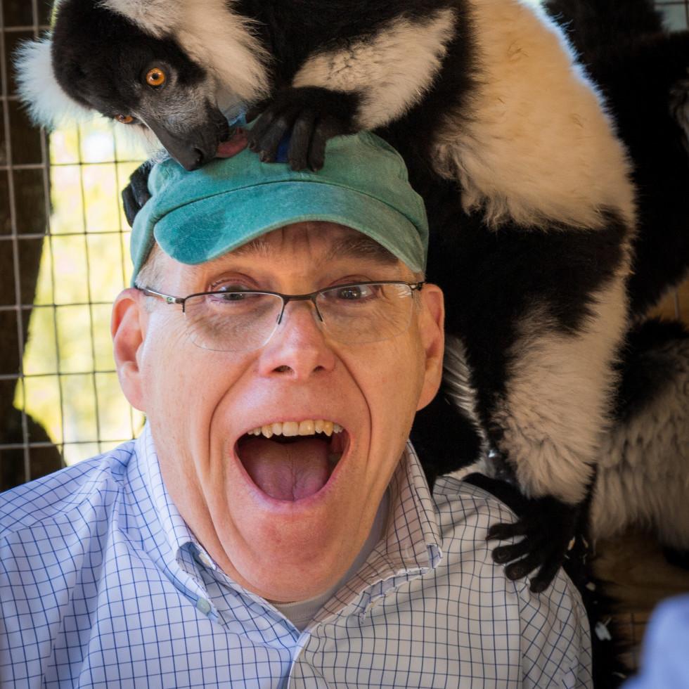 Man with a lemur on his head