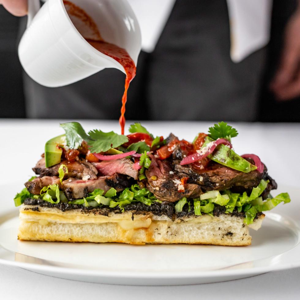 The Annie Cafe open-face steak sandwich with Creamy Black Beans, Avocado & Drunken Chili Sauce