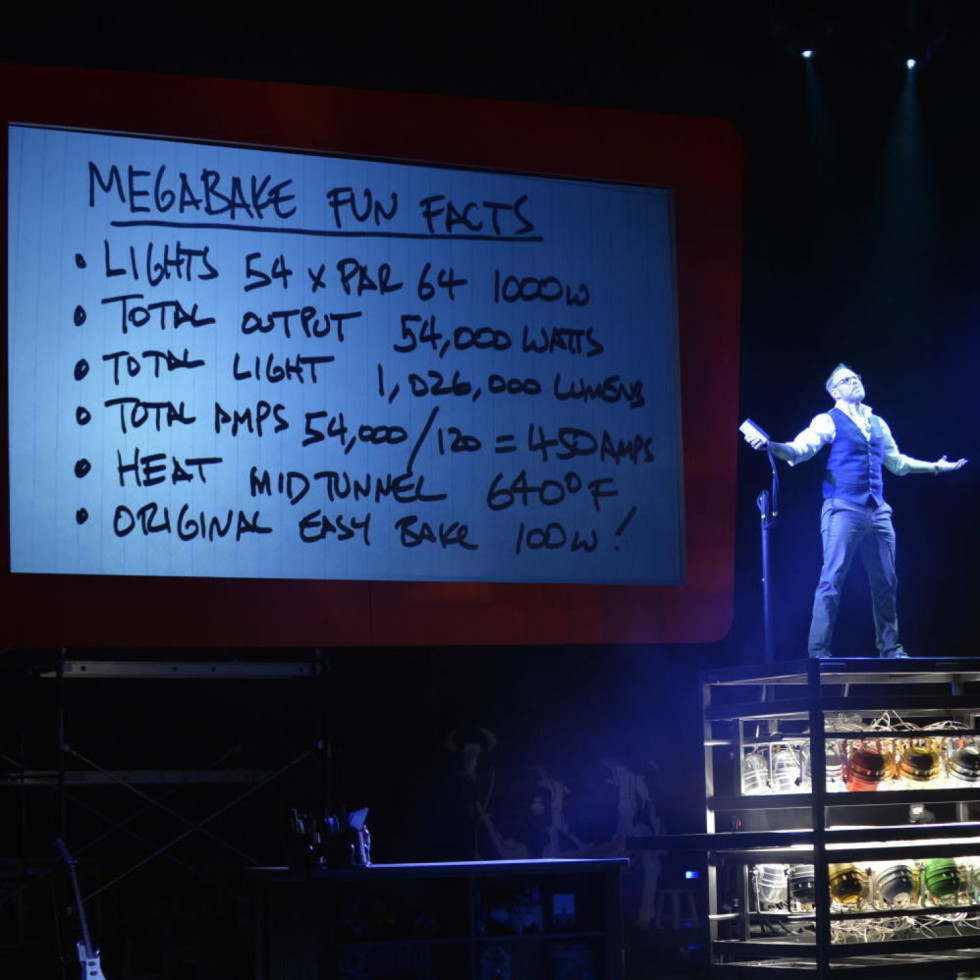 Alton Brown stands on top of a metal rack onstage in front of oven notes.