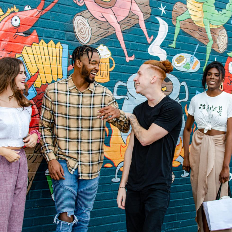 Group outside restaurant mural