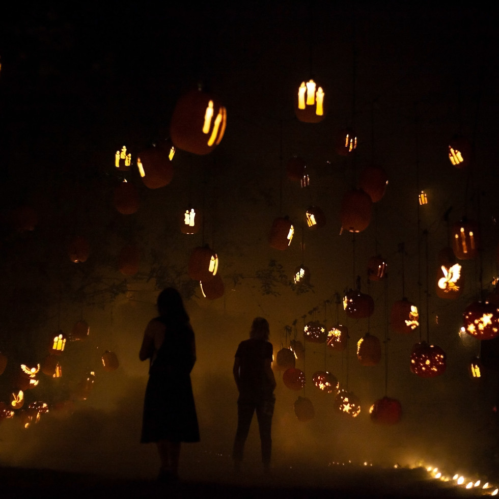 Two shadowed figures wander through a hall of floating jack-o-lanterns in mist.