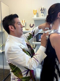 Daniel Esquivel pins and tucks a garment under construction during a fitting.