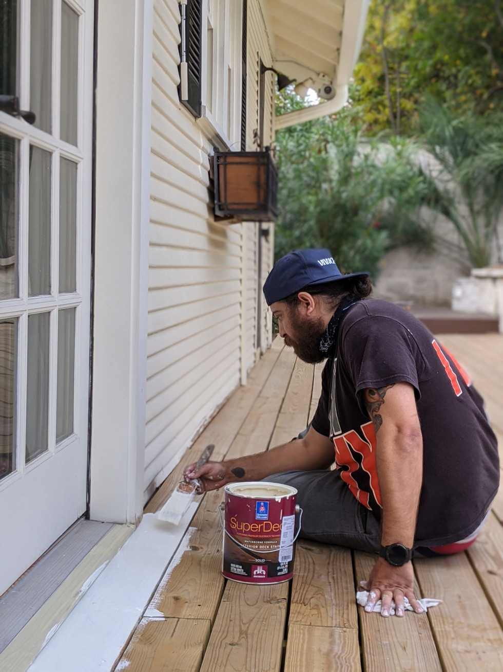 A member of The Handyband Collective sits on a pool deck, trimming the wood against the house with a white paint brush.