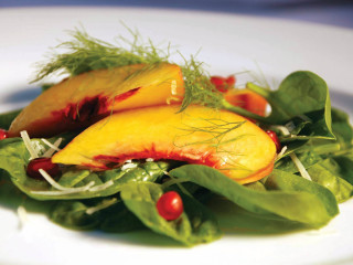 Salad with peaches and pomegranate at Canary by Gorgi in Addison