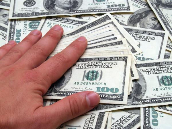 hand on money $100 bills getting rich