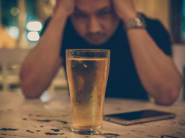 Man alone at bar drinking beer