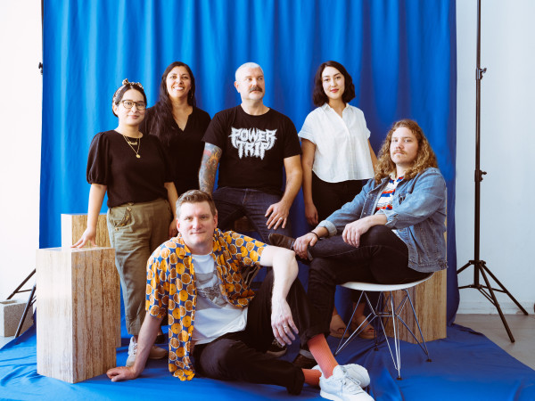 The team launching concert promotion and creative branding company Resound, sitting in front of a blue backdrop with photo equipment