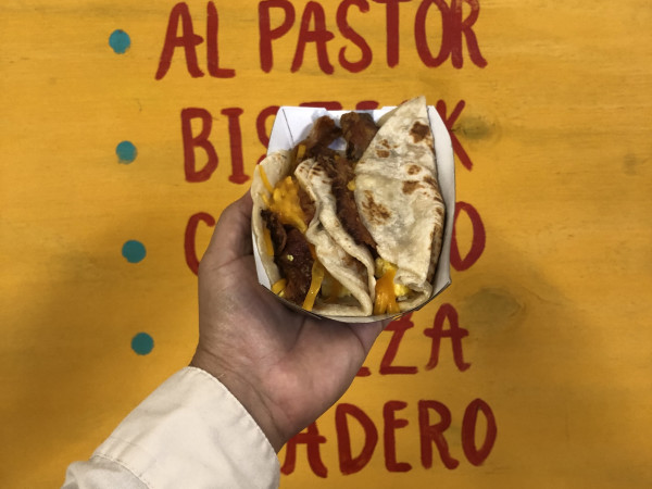 A hand displays a taco in front of a handwritten menu.