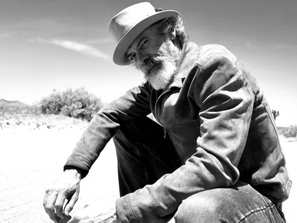 Actor and musician Tommy Howell poses in suede in a desert landscape.