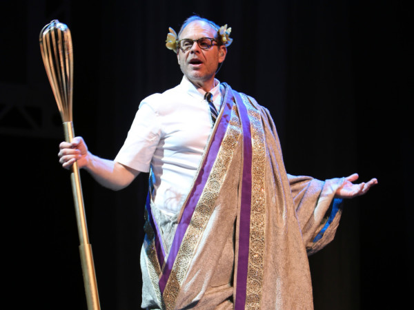 Celebrity chef and TV host Alton Brown poses onstage in a toga with a giant whisk.