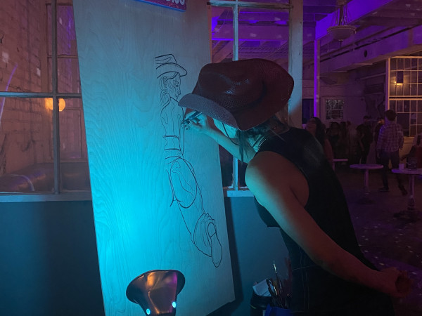 """AJ Brooker works on a line drawing of a nude cowgirl at the Swan Dive during the """"Saddle Up"""" event."""