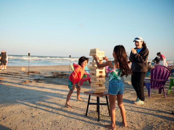 Family playing Jenga on the beach