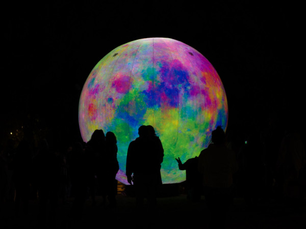 An audience looks at a large colorful sphere at the Luminaria Contemporary Arts Festival.