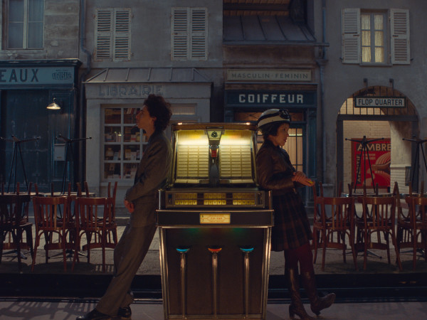 A still from The French Dispatch shows two figures facing away from each other on a French street at night.