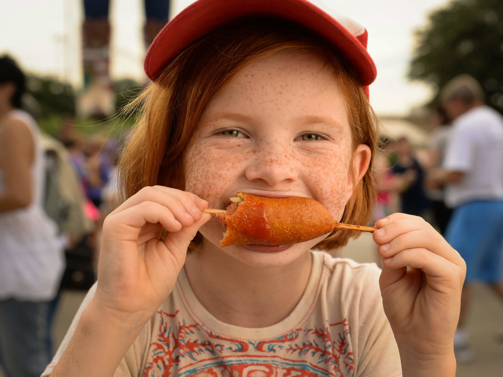 Child eating a corn dog at the State Fair of Texas