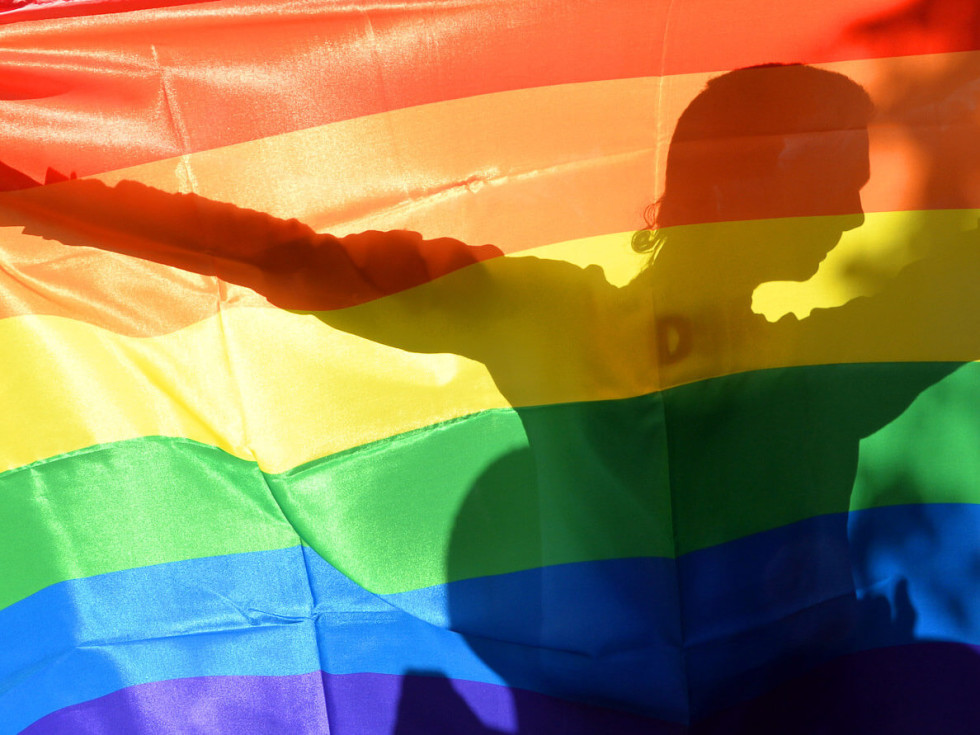 rainbow flag with person silhouetted behind it