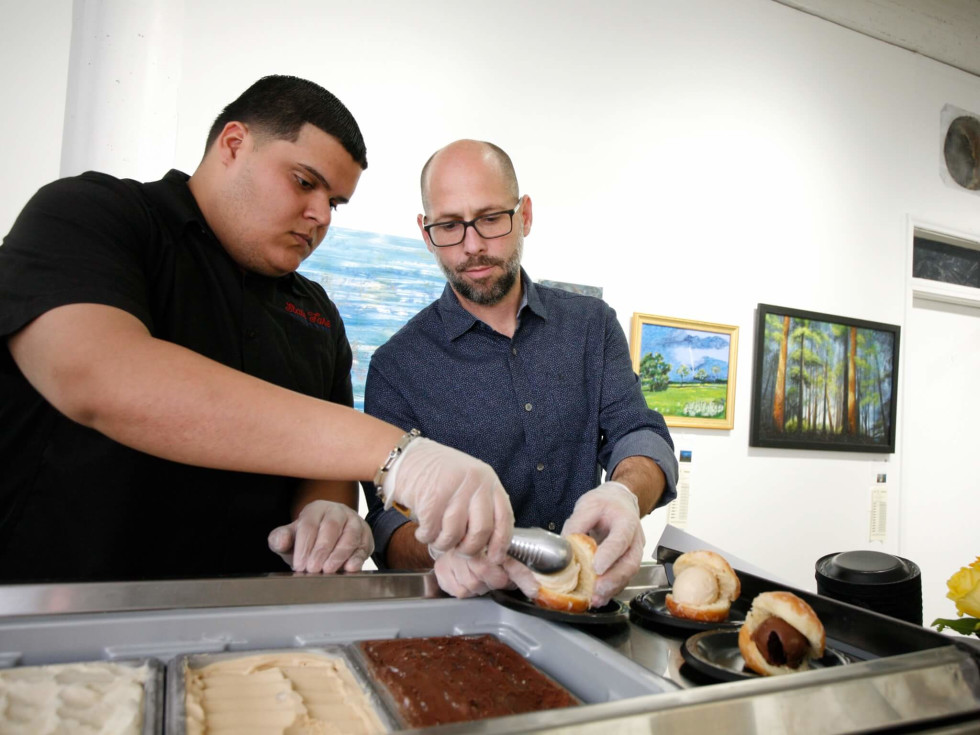 Luis Santana and Jason Richburg of Lee's Creamery prepare doughnut ice cream sandwiches for Preview Party guests at Art on the Avenue.