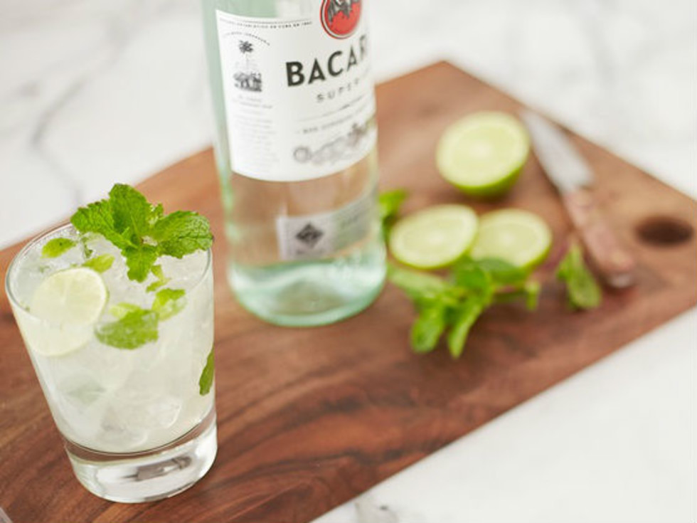 Cocktail and bottle of Bacardi on a cutting board