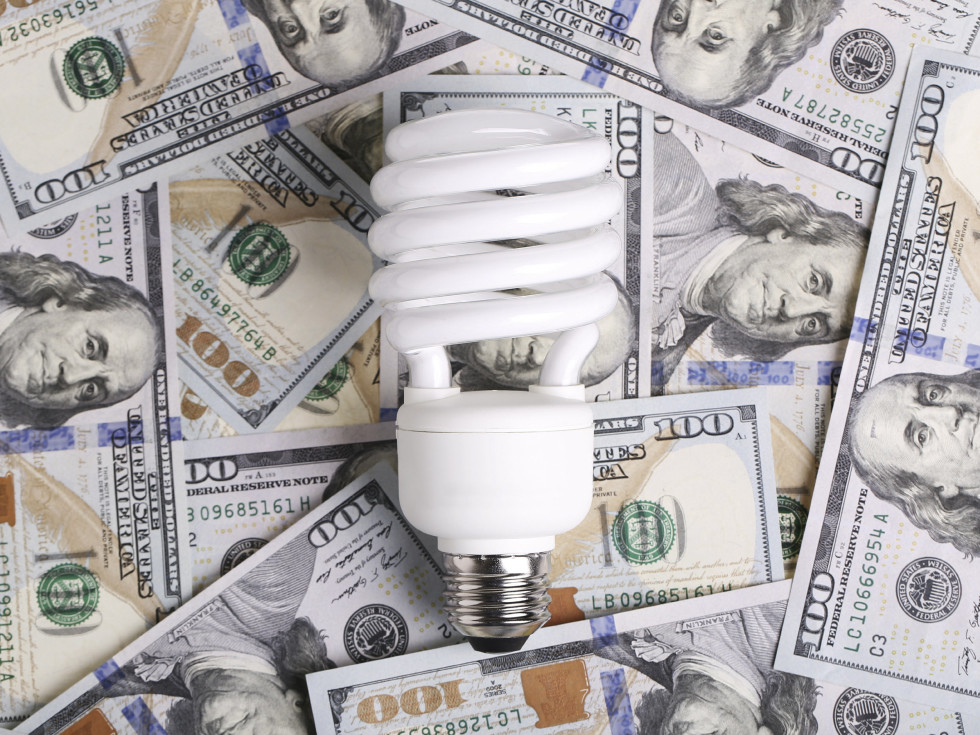 Compact fluorescent light bulb on a pile of cash