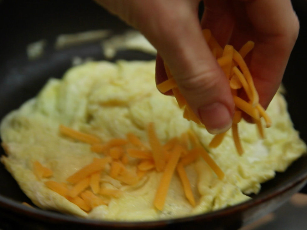 Adding shredded cheese to an omelet