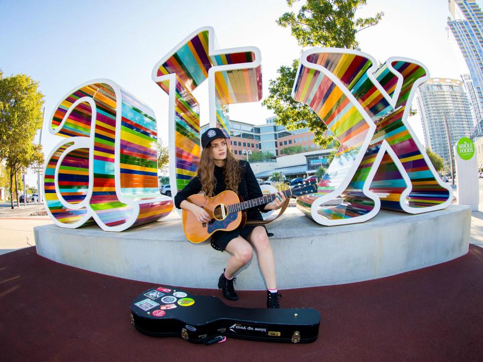 Jane Ellen Bryant performs at HAAM Benefit Day ATX sign