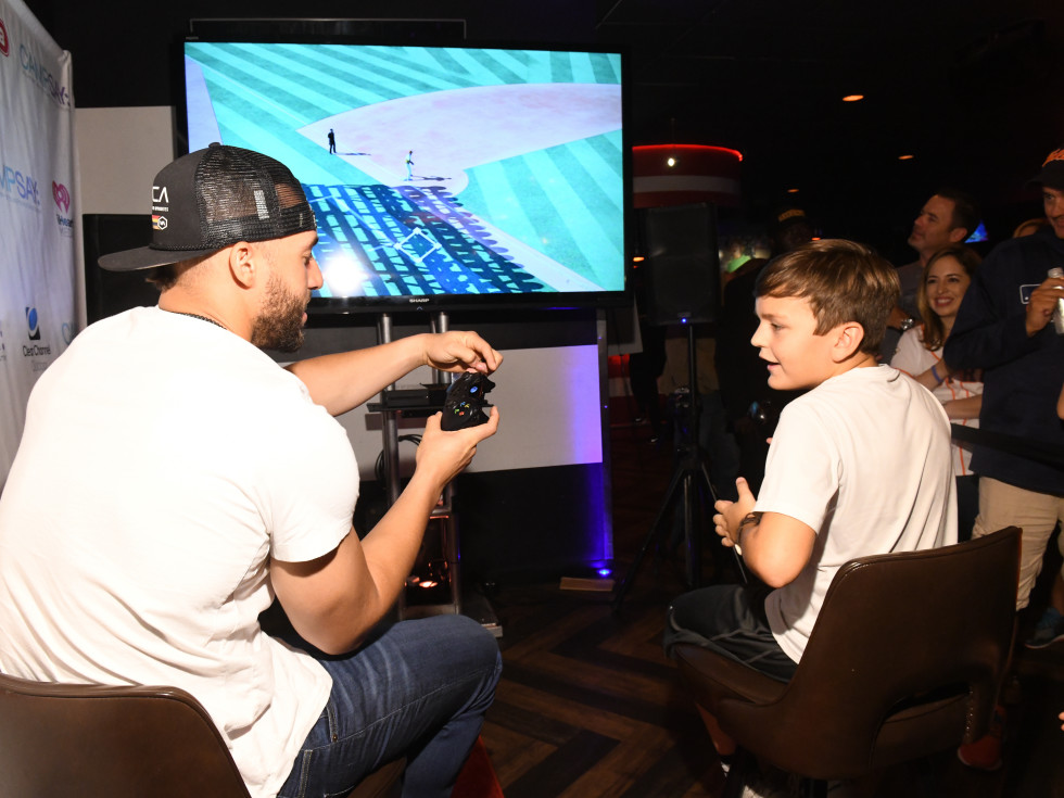 George Springer playing video game with auction winner
