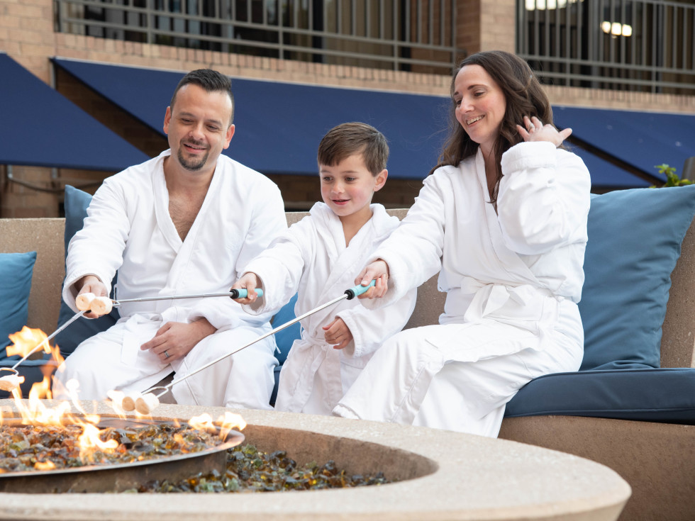 Family making s'mores poolside