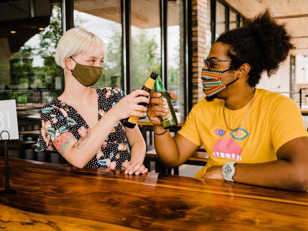 Masked people having a beer
