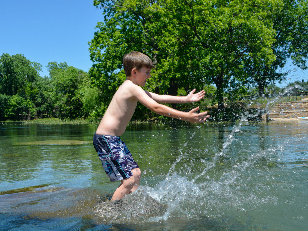 Boy splashing in the San Marcos River