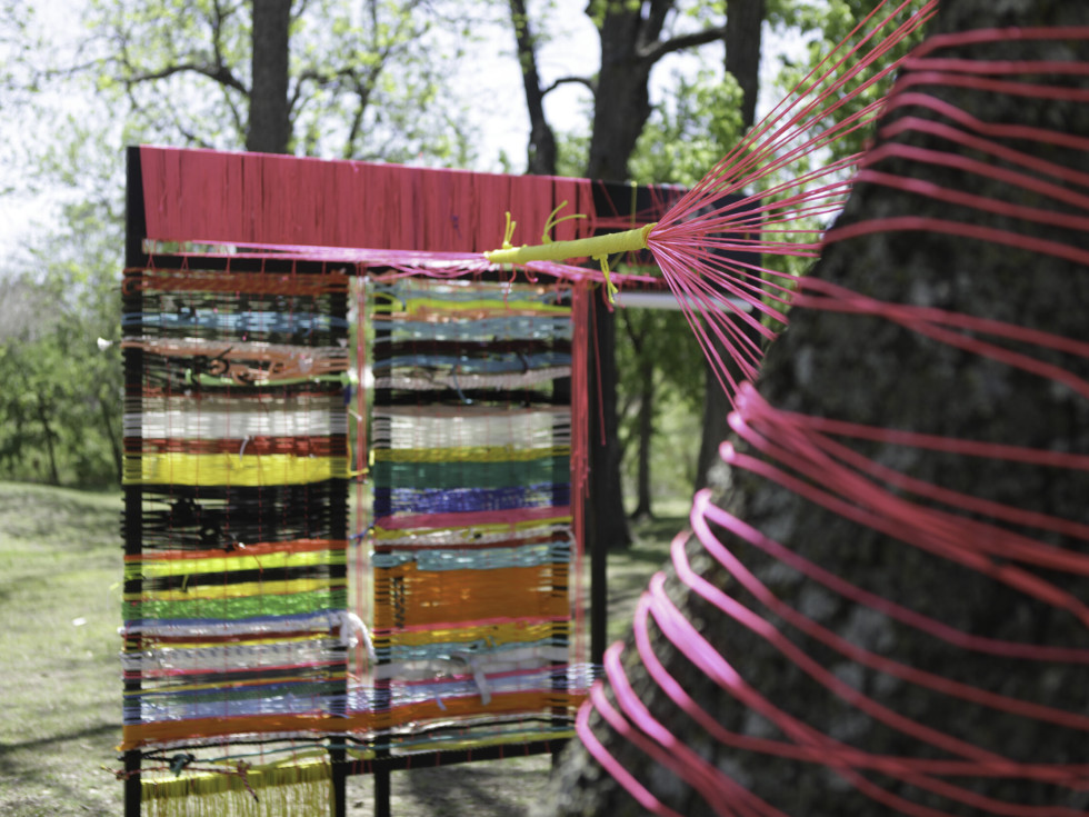 Mire + Mend, a community art project weaves colorful fabric and ropes between trees outside the Elisabet Ney Museum.