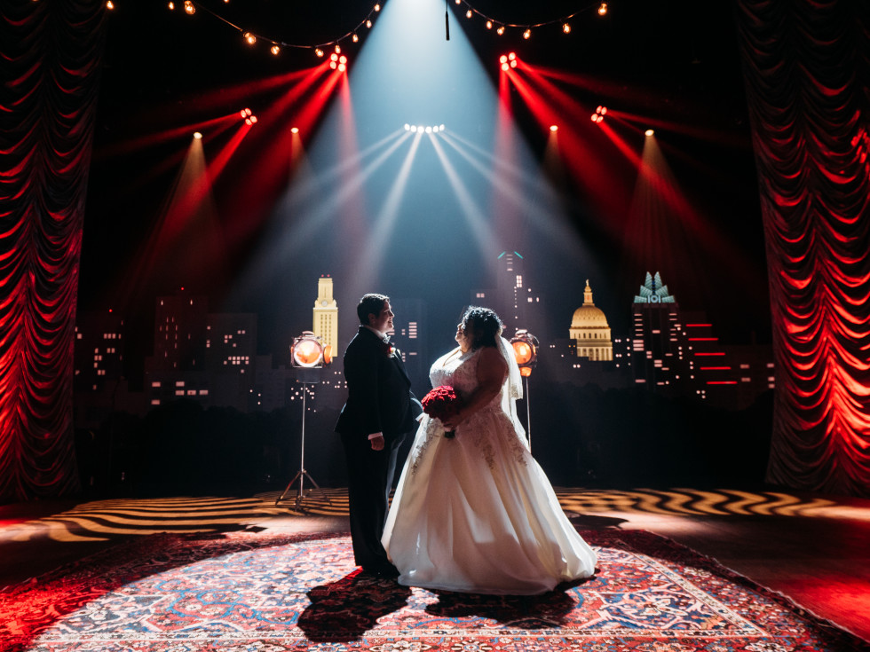 A couple stands smiling at each other in a wedding dress and tuxedo, in front of red curtains and the recognizable skyline backdrop at Austin City Limits Live.