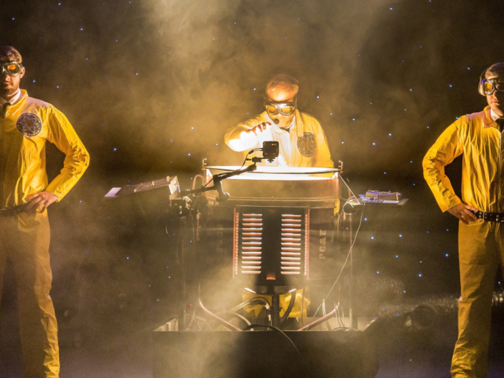 Alton Brown and two assistants stand in yellow hazmat suits around a mysterious contraption.