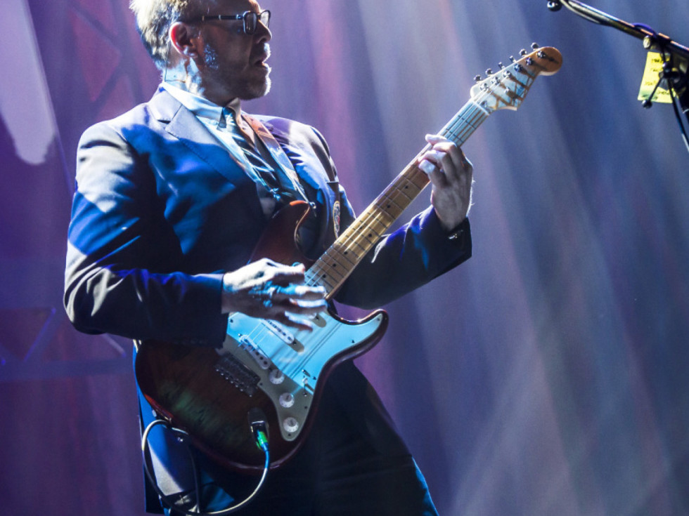 Alton Brown plays an electric guitar onstage.