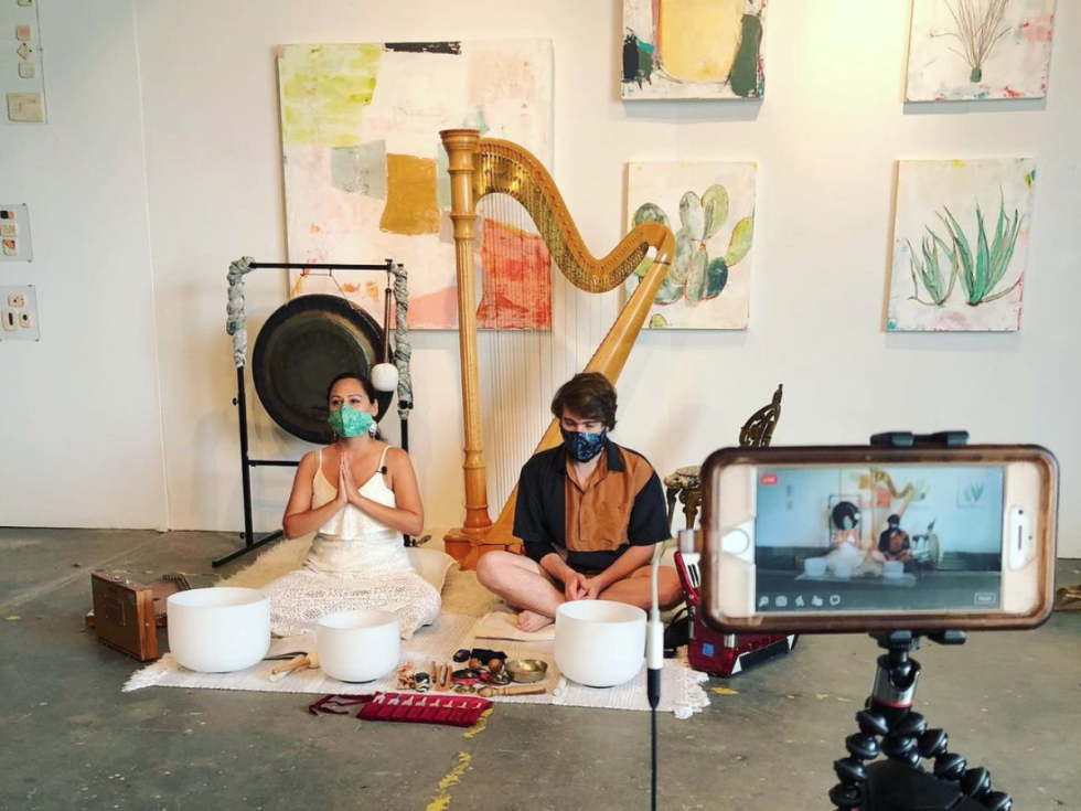 Two musicians sit among crystal singing bowls, a harp and paintings.