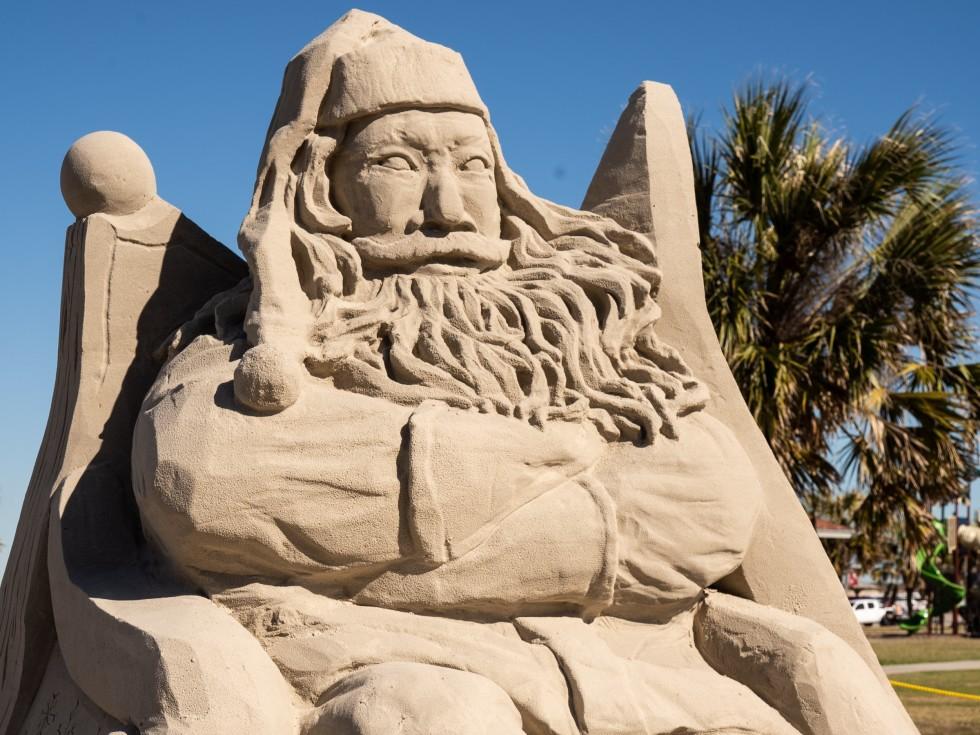 Santa Claus sand sculpture with kids