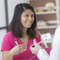 Woman in pink shirt talking to doctor