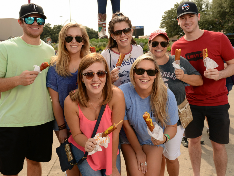People eating corn dogs at State Fair of Texas