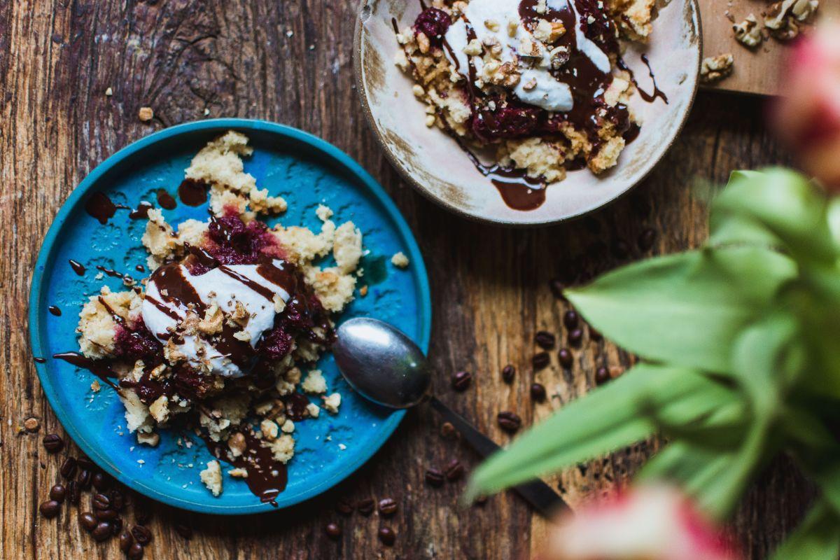 Veganska grmada s kavnim okusom, višnjevo marmelado, kokosovo smetano, čokolado in orehi.