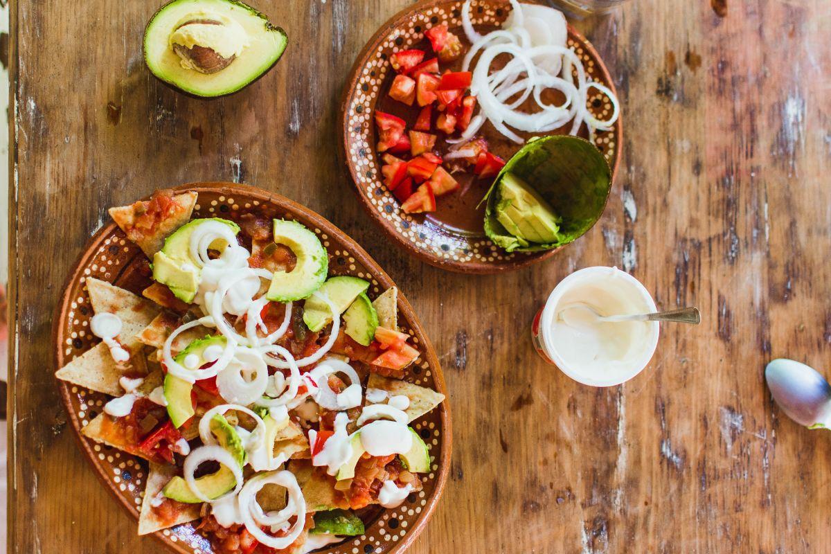 jed chilaquiles iz ocvrtih tortilj ter dodatki
